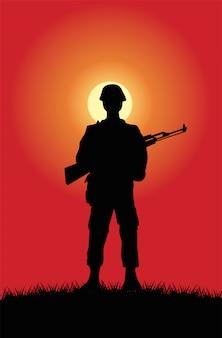 Soldaat met het silhouet van het geweercijfer bij zonsondergangscène