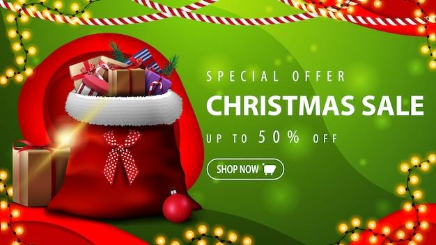 Speciale aanbieding, kerstuitverkoop, tot 50% korting, groene horizontale kortingsbanner in papier gesneden stijl met kerstman tas met cadeautjes