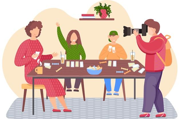 Spelen van bordspel met kaarten thuis en gelukkige familie. een mannenfotograaf maakt een foto van moeder en kinderen. moeder, zoon en dochter zitten samen aan een tafel. leuke avond tijdens een familieweekend