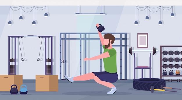 Sport man doet squats oefeningen met kettlebell kerel training cardiotraining concept moderne sportschool gezondheid studio club interieur horizontale volledige lengte
