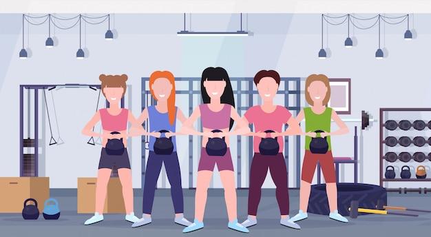 Sport mensen groep doen oefeningen met kettlebell meisjes met kerel training in gym training gezonde levensstijl concept moderne healthclub studio interieur horizontaal