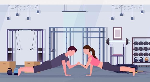 Sport paar doen sterkte planking oefening gespierde man vrouw hand in hand training samen training gezonde levensstijl concept moderne health club gym interieur horizontale vlak
