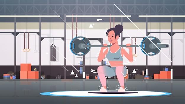 Sportief meisje doet squats oefeningen met barbell dynamische sportvrouw