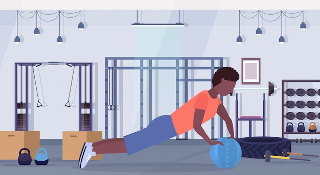 Sportieve man crossfit oefeningen doen met geneeskunde lederen bal afro-amerikaanse man training cardiotraining concept moderne sportschool gezondheid studio club interieur horizontale volledige lengte