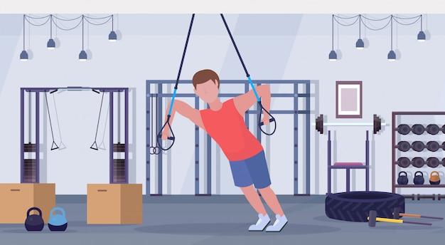 Sportieve man doen oefeningen met vering fitness riemen elastische touw man opleiding crossfit training concept moderne sportschool studio interieur horizontale platte volledige lengte