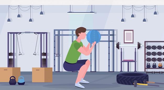 Sportieve man squats oefeningen doen met geneeskunde lederen bal kerel training cardiotraining concept moderne sportschool gezondheid studio club interieur horizontale volledige lengte