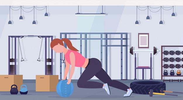 Sportieve vrouw crossfit oefeningen doen met geneeskunde lederen bal meisje training cardiotraining concept moderne sportschool gezondheid studio club interieur horizontale volledige lengte