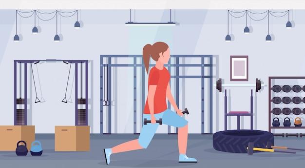 Sportieve vrouw die hurkzit met domoren doen meisje opleiding in gymnastiekbillen training gezonde levensstijl concept moderne healthclub studio interieur horizontaal