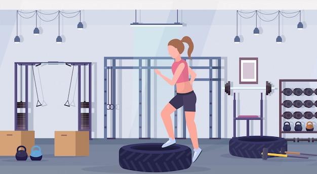 Sportieve vrouw die hurkzit op bandenplatform doen meisje opleiding benen training gezonde levensstijl crossfit concept moderne sportschool interieur horizontale flat