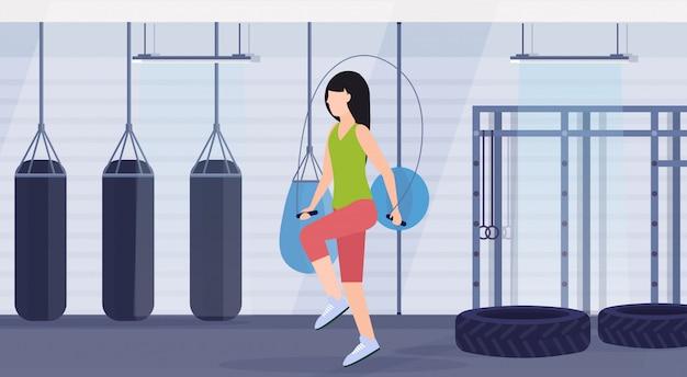 Sportieve vrouw die oefeningen met touwtjespringen meisje training crossfit training gezonde levensstijl concept platte moderne strijd club met bokszakken gym interieur horizontale doet
