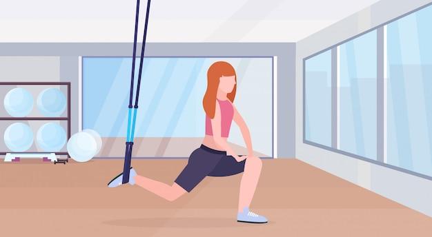 Sportieve vrouw doet squats oefeningen met schorsing fitnessriemen elastische touw meisje training crossfit training concept moderne sportschool health club studio interieur horizontale volledige lengte