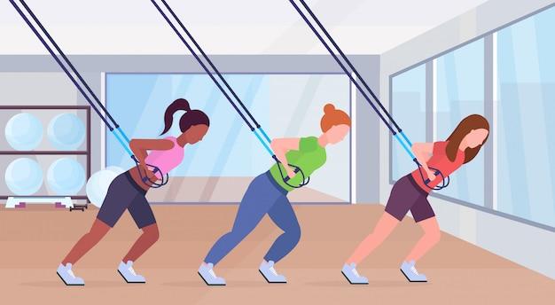 Sportieve vrouwen die oefeningen doen met ophanging fitnessriemen elastisch touw mix tace meisjes training groep klassen crossfit workout concept modern gym studio interieur horizontaal volledige lengte