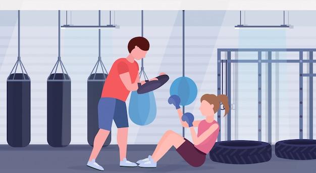 Sportvrouw bokser boksen oefeningen met personal trainer meisje vechter in blauwe handschoenen uit te werken op vloer strijd clubwith bokszakken gym interieur gezonde levensstijl concept horizontaal