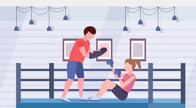 Sportvrouw bokser boksen oefeningen met persoonlijke trainer meisje vechter in blauwe handschoenen uit te werken op vloer strijd club ring arena interieur gezonde levensstijl concept