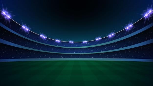 Stadion met verlichting, groen gras en nachthemel.