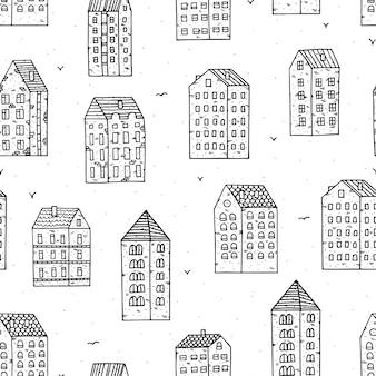 Stads naadloos patroon met hand getrokken huizen in krabbelstijl op witte achtergrond.