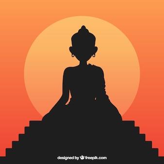 Standbeeld van het silhouet van boedha met zonsondergang
