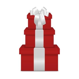 Stapel van drie realistische rode geschenkdozen met wit lint en boog