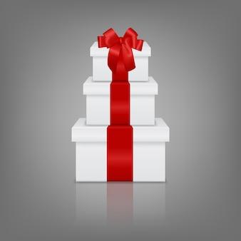 Stapel van drie realistische witte geschenkdozen met rood lint en boog