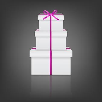Stapel van drie realistische witte geschenkdozen met roze lint en boog