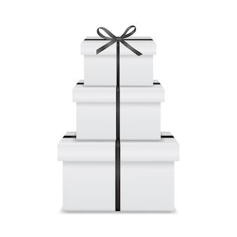 Stapel van drie realistische witte geschenkdozen met zwart lint en strik