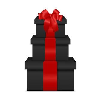 Stapel van drie realistische zwarte geschenkdozen met rood lint en boog