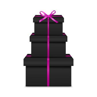 Stapel van drie realistische zwarte geschenkdozen met roze lint en boog