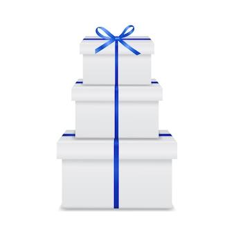 Stapel witte geschenkdozen met blauw lint en boog