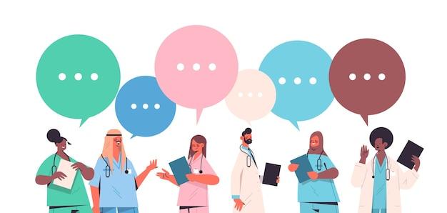 Stel mannelijke vrouwelijke artsen in uniform met praatjebellen communicatie gezondheidszorg geneeskunde concept mix race medische arbeiders collectie horizontaal portret