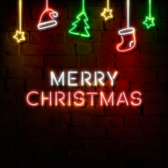 Sterren, kerstmuts, kous, pijnboom en merry christmas-neonteken op een donkere bakstenen muur