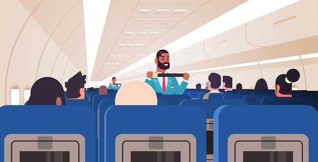 Steward legt passagiers uit hoe de gordelbevestiging te gebruiken in een noodsituatie afro-amerikaanse stewardessen in uniform veiligheidsdemonstratieconcept vliegtuigbord interieur horizontaal