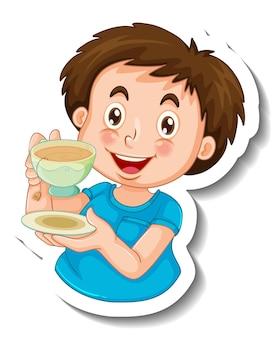 Stickersjabloon met een gelukkige jongen die een kopje thee geïsoleerd houdt