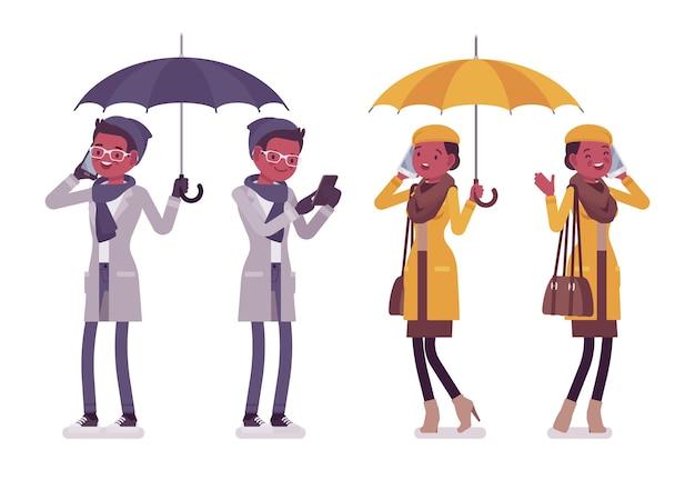 Stijlvolle jonge zwarte man en vrouw met gadgets die de illustratie van de herfstkleren dragen