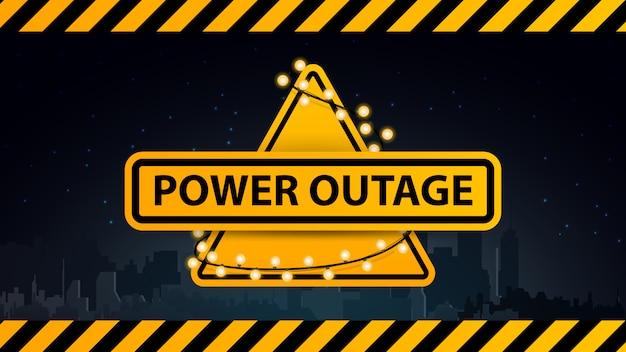 Stroomuitval, geel waarschuwingslogo omwikkeld met een slinger op de achtergrond van de stad zonder elektriciteit