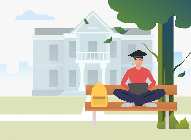 Student die en laptop op bank in campuspark bestudeert gebruikt