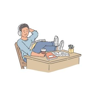 Student in hoofdtelefoons met kopje koffie zittend met zijn benen op tafel gegooid en boek lezen