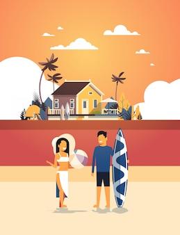 Surfer paar zomervakantie man vrouw surfplank op zonsondergang strand villa huis tropisch eiland verticaal