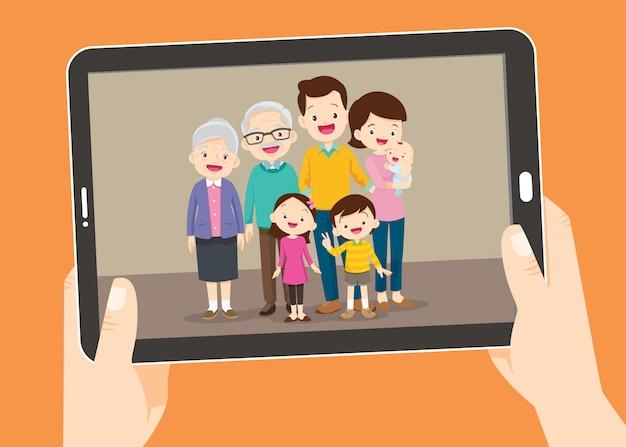 Tablet pc met de familiefoto, handen met touchscreen tablet pc