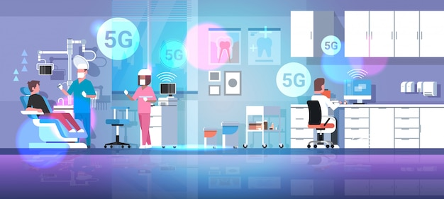 Tandarts met assistent boortanden van mannelijke patiënt 5g online draadloze verbinding concept
