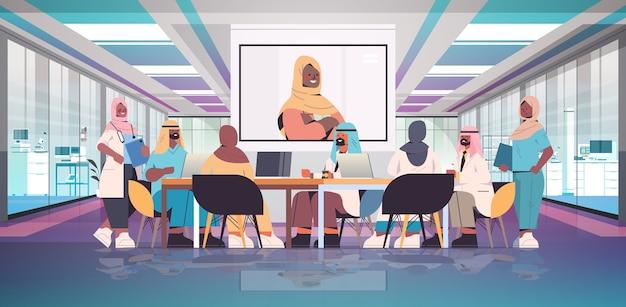 Team van arabische medische specialisten met videoconferentie met vrouwelijke zwarte moslim arts geneeskunde gezondheidszorg concept ziekenhuis vergaderzaal interieur horizontale volledige lengte vectorillustratie