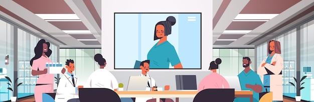 Team van artsen met videoconferentie mix race medische professionals bespreken aan ronde tafel geneeskunde gezondheidszorg concept ziekenhuis interieur horizontaal portret vectorillustratie
