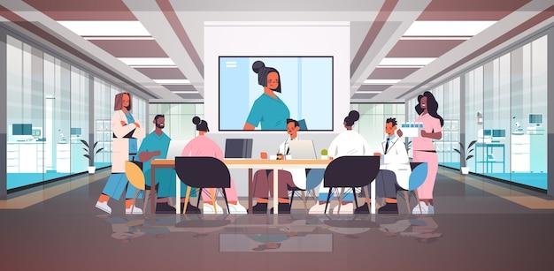 Team van artsen met videoconferentie mix race medische professionals bespreken aan ronde tafel geneeskunde gezondheidszorg concept ziekenhuis interieur horizontale volledige lengte vectorillustratie