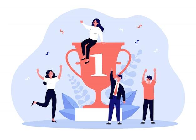 Team van gelukkige winnaars die rond toekenningstrofee vieren