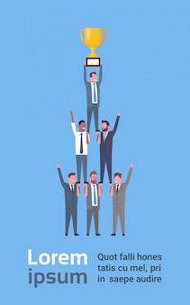 Team van succesvolle bedrijfsmensen die gouden kop, zakenliedensucces en teamwork concept houden