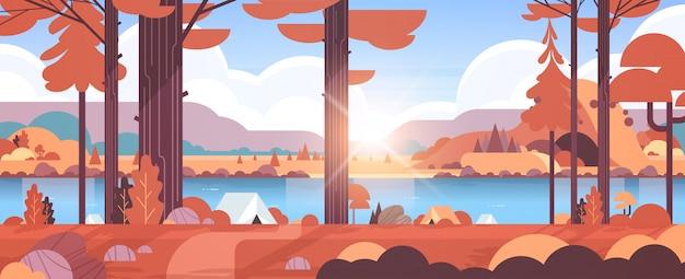 Tenten kampeerterrein in bos zomerkamp concept zonnige dag zonsopgang herfst landschap natuur met water bergen en heuvels