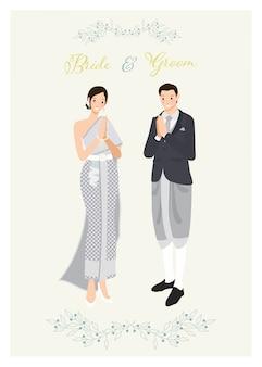 Thais paar in traditioneel lichtblauwgrijs donker kostuum en de uitnodigingsmalplaatje van het kledingshuwelijk