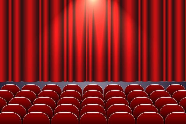 Theaterzaal met rijen rode stoelen en podium met gordijn