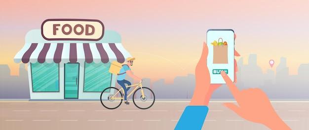 Thuis eten bestellen. de man heeft het geluk om eten op de fiets te bestellen. hand houdt smartphone.