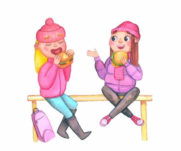 Tienermeisjes in jassen en gebreide mutsen zitten op de borstwering en eten een hamburger, lachend en pratend