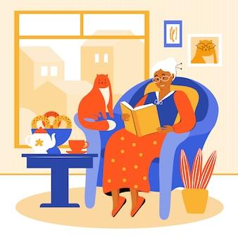 Tijdens de quarantaine blijft een oudere vrouw thuis. oma zit in een stoel bij het raam een boek te lezen. gepensioneerde drinkt thee met zelfgemaakt gebak. oude vrouw brengt tijd door met haar huisdier